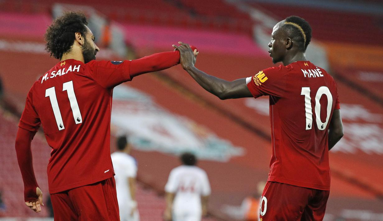 Penyerang Liverpool, Sadio Mane, melakukan selebrasi bersama Mohamed Salah usai membobol gawang Crystal Palace pada laga Premier League di Stadion Anfield, Rabu (24/6/2020). Liverpool menang dengan skor 4-0. (AP/Phil Noble)