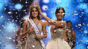 Miss Valle del Cauca Valeria Morales (kiri) menerima mahkota Miss Colombia 2018 dari Laura Gonzales selama kontes kecantikan Miss Colombia di Medellin (30/9). Wanita 20 tahun ini lahir di Santiago de Cali pada 2 Januari 1998. (AFP Photo/Joaquin Sarmiento)