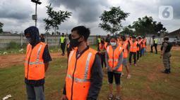 Sejumlah pelanggar PSBB bersiap doa di makam korban Covid-19 di TPU Jombang, Tangerang Selatan, Senin (18/1/2020). 17 pelanggar PSBB tersebut dihukum untuk berdoa di makam korban Covid-19. (merdeka.com/Arie Basuki)