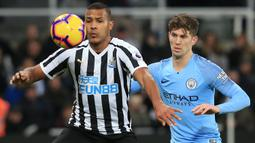 Striker Newcastle United, Salomon Rondon, berebut bola dengan bek Manchester City, John Stones, pada laga Premier League di Stadion James Park, Selasa (29/1). Newcastle United menang 2-1 atas Manchester City. (AFP/Lindsey Parnaby)