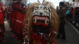 Peserta mengenakan kostum reog saat mengikuti karnval budaya untuk memeriahkan HUT ke-19 kota Depok di Sepanjang Jalan Margonda, Depok, Sabtu (28/4). (Merdeka.com/Imam Buhori)