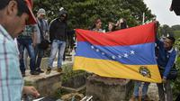Bendera negara Venezuela dibentangkan saat prosesi pemakaman Jose Francisco Guerrero di San Cristobal, Tachira State, Venezuela (19/5). (AFP/Luis Robayo)