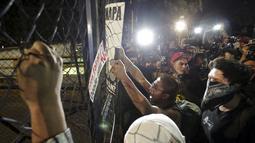 Sejumlah pengunjuk rasa melakukan protes di dekat kediaman presiden di Mexico City, Meksiko, (26/11). Ratusan aktivis turun kejalan untuk menuntut keadilan 43 siswa yang hilang. (REUTERS/Daniel Becerril)