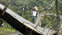 Warga melewati jembatan gantung bersejarah yang ambruk akibat putus tali di Batu Busuak, Padang, Sumbar. (Antara)