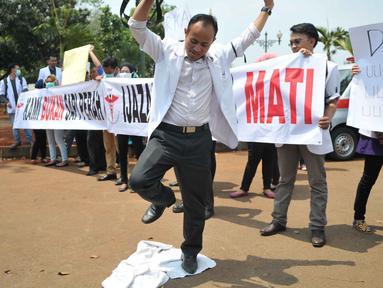 Massa menginjak jas putih khas dokter saat melakukan unjuk rasa di depan Istana Merdeka, Jakarta, Senin (7/9/2015). Mereka memprotes Kemenristek Dikti yang telah menahan ijazah fakultas kedokteran mereka. (Liputan6.com/Gempur M Surya)