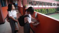 Siswa mencuci tangan saat uji coba pembelajaran tatap muka (PTM) terbatas di SMAN 1 Kota Tangerang, Banten, Senin (6/9/2021). Dinas Pendidikan Provinsi Banten uji coba PTM di SMA di Kota Tangerang secara terbatas dengan bergiliran dan menerapkan protokol kesehatan ketat. (Liputan6.com/Angga Yuniar)