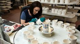 Pekerja melukis dengan tangan sebuah mug untuk merayakan pernikahan Pangeran Harry dan Meghan Markle di pabrik Emma Bridgewater di Stoke-on-Trent, Inggris (16/4). (AFP/Oli Scarff)