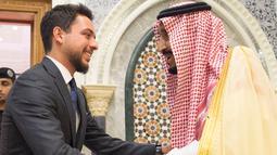 Raja Arab Saudi Salman bin Abdulaziz (kanan) bersalaman dengan Putra Mahkota Yordania Hussein bin Abdullah (kiri) saat membahas krisis ekonomi Yordania di Mekah, Arab Saudi, Senin (11/6). (Bandar Al-Jaloud/Saudi Royal Palace/AFP)