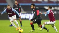 Penyerang Liverpool, Mohamed Salah, berebut bola dengan pemain West Ham United, Aaron Cresswell, pada laga Liga Inggris di Stadion London, Minggu (31/1/2021). Liverpool menang dengan skor 3-1. (Clive Rose/Pool via AP)