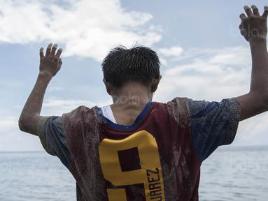 Pesepak bola SSB Tulehu Putra, Rizki Lestaluhu, mengangkat tangan saat  latihan di tepi Pantai Tial, Maluku, Rabu (16/11/2017). Dirinya merupakan salah satu pemain muda berbakat dari Negeri Tulehu. (Bola.com/Vitalis Yogi Trisna)