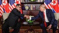 Presiden Amerika Serikat (AS) Donald Trump  dan Pemimpin Korea Utara, Kim Jong-un bersalaman dalam pertemuan bersejarah di resor Capella, Pulau Sentosa, Selasa (12/6). Trump dan Kim menyempatkan diri untuk menyapa jurnalis. (AP/Evan Vucci)