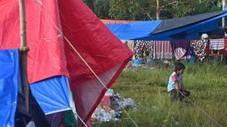 Seorang gadis duduk di antara tenda-tenda saat orang-orang yang terkena dampak tinggal di kamp sementara di Mamuju, Senin (18/1/2021). Gempa berkekuatan magnitudo 6,2 yang terjadi pada Jumat (15/1) dini hari mengakibatkan puluhan orang meninggal dunia. (AFP/Adek Berry)