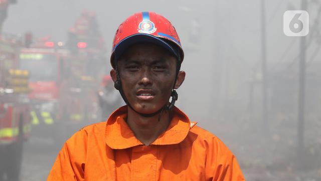 Ekspresi petugas pemadam kebakaran seusai memadamkan api di lapak ban bekas, Desa Bojong Nangka, Gunung Putri, Bogor, Kamis (22/4/2021). Kebakaran lapak ban bekas yang terjadi Senin (19/4) petang tersebut hingga saat ini belum bisa dipadamkan. (Liputan6.com/Herman Zakharia)