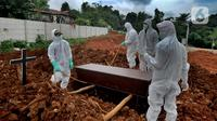 Petugas melakukan pemakaman korban COVID-19 di TPU Jombang, Tangerang Selatan, Banten, Senin (18/1/2021). Sudah dua minggu terakhir terjadi penambahan pemakaman korban COVID-19 di TPU Jombang. (merdeka.com/Arie Basuki)