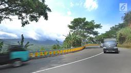 Kendaraan melintas dekat teknologi roller barrier di tanjakan letter S Kampung Bantarselang, Kecamatan Cikidang, Sukabumi, Minggu (6/1). Roller barrier ini diklaim lebih efektif daripada pembatas beton atau besi yang memanjang. (Merdeka.com/Arie Basuki)