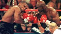 Mike Tyson dan Evander Holyfield kembali berduel di MGM Grand Garden Arena, Las Vegas pada 28 Juni 1997. Akan tetapi, laga akbar ini harus dihentikan pada ronde ketiga, karena Tyson menggigit kuping Holyfield. (AFP/JOHN GURZINSKI)