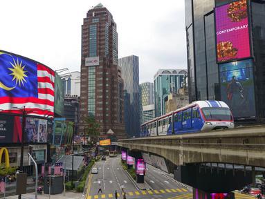 Sebuah LRT (Light Rain Transit) melewati papan bendera Nasional di Kuala Lumpur, Malaysia, Selasa (14/9/2021). Malaysia pecah rekor tembus dua juta kasus Covid-19 dengan tambahan 15.669 kasus Selasa (14/9/2021). (AP Photo/Vincent Thian)
