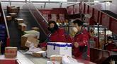 Kurir sibuk memilah paket di pusat distribusi di Beijing, China, Selasa (18/2/2020). Wabah virus corona atau COVID-19 membuat warga memilih untuk tinggal di rumah dan memanfaatkan jual beli secara online. (AP Photo/Ng Han Guan)