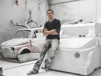 Seniman Italia, Nazareno Biondo berpose dengan replika mobil Fiat 500 berbahan dasar marmer Carrara pahatannya di Cafasse, dekat Turin, Italia, Rabu (16/5). (MARCO BERTORELLO/AFP)