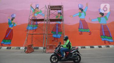 Pengendara motor melintas di Flyover 'Gaplek' Martadinata yang dipercantik dengan lukisan mural di Tangerang Selatan, Jumat (9/4/2021). Seni mural ini untuk memperindah suasana jalan kota. (merdeka.com/Imam Buhori)