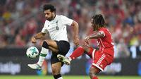Penyerang Liverpool, Mohamed Salah berusaha mengontrol bola dari kawalan gelandang Munchen, Renato Sanches saat bertanding di semifinal Audi Cup di Allianz Arena di Munich, Jerman (1/8). Liverpool menang 3-0 atas Munchen. (Christof Stache/AFP)