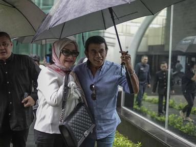 Rhoma Irama memayungi istrinya Ricca Rachim saat hadir dalam konferensi pers indosiar Ramadhan Penuh Berkah di Jakarta, Kamis (26/4). Rhoma Irama terlihat romantis saat memayungi istrinya Ricca Rachim. (Liputan6.com/Faizal Fanani)