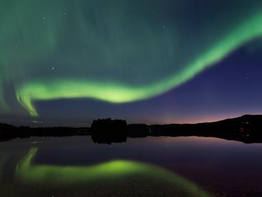 Cahaya aurora borealis menerangi langit malam Desa Erikslund di Vasternorrland County, Swedia (23/8). Fenomena alam yang indah ini terjadi pada bulan Maret-April dan September-Oktober. (AFP PHOTO/ JONATHAN NACKSTRAND)