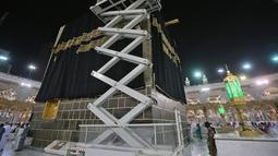Petugas saat mengganti kain penutup Ka'bah (Kiswah) dengan yang baru di Masjidil Haram, kota suci Makkah, Arab Saudi (18/7/2021). Pergantian Kiswah rutin dilakukan pada musim haji, tepatnya pada 9 Zulhijah. (AFP Photo)