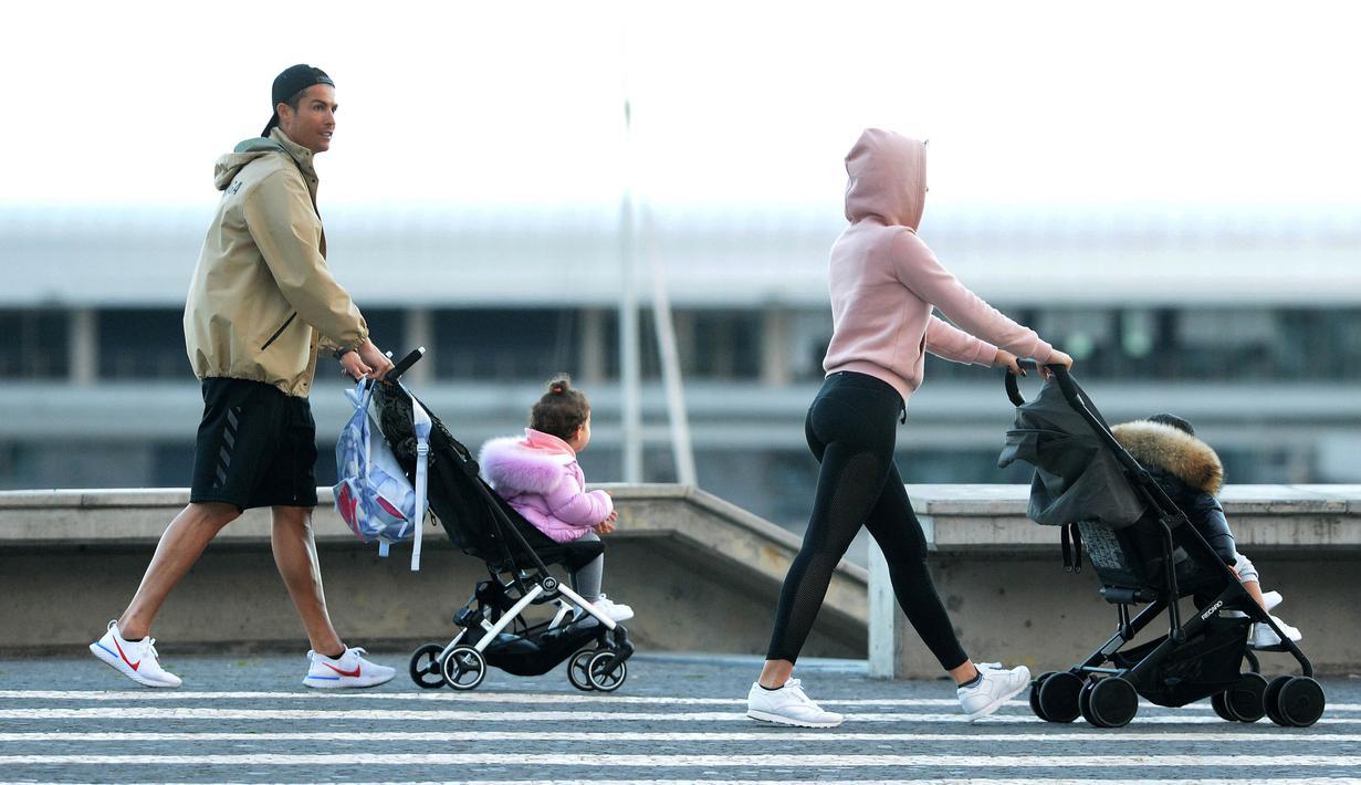 Cristiano Ronaldo bersama kekasihnya Georgina Rodriguez mengajak anak-anaknya berjalan santai di Funchal, Portugal, Sabtu (28/3/2020). Bintang Juventus ini memilih pulang kampung saat Serie A dihentikan sementara karena wabah virus corona. (AFP/Helder Santos)