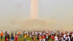 Suasana saat warga bermain serbuk warna-warni saat Festival Damai Millenial Road Safety di Monas, Jakarta, Minggu (23/6/2019). Serbuk warna-warni yang ditembakkan oleh meriam menambah kemeriahan Festival Damai. (merdeka.com/Iqbal Nugroho)