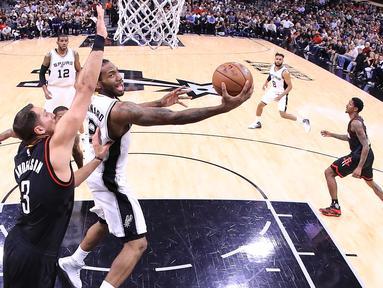 Pemain Spurs, Kawhi Leonard (2) berusaha memasukan bola ke ring di gim kelima semifinal wilayah barat Playoffs NBA 2017 di AT&T Center, San Antonio, Texas (9/5). Spurs mengalahkan Rockets 110-107 lewat overtime. (Ronald Martinez/Getty Images/AFP)