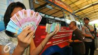 Seorang wanita menunjukan beberapa mata uang baru di Blok M, Jakarta, Senin (19/12). Bank Indonesia (BI) hari ini meluncurkan 11 uang rupiah Emisi 2016 dengan gambar pahlawan baru. (Liputan6.com/Angga Yuniar)