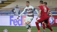 Kapten Timnas Portugal, Cristiano Ronaldo, saat coba melewati kawalan pemain Serbia pada laga kedua Grup A kualifikasi Piala Dunia 2022 di Stadion Rajko Mitic, Minggu (28/3/2021) dini hari WIB. (Pedja Milosavljevic/AFP)