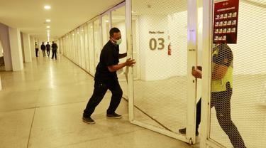 Petugas menutup salah satu pintu Stadion Madya usai dibatalkannya pertandingan antara Timnas Indonesia melawan Tira Persikabo karena tak mendapatkan izin dari Kepolisian Republik Indonesia. (Foto: Bola.com/M. Iqbal Ichsan)