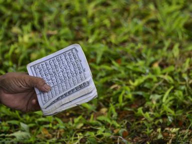 Seorang perempuan membaca Alquran pada peringatan 16 tahun gempa bumi dan tsunami Aceh di sebuah kuburan massal di Siron, Sabtu (26/12/2020).  Peringatan di tengah pandemi COVID-19 itu tetap berlangsung secara sederhana melalui kegiatan ziarah kubur. (CHAIDEER MAHYUDDIN/AFP)
