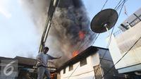 Warga berusaha memadamkan api yang membakar pemukiman penduduk di Tanah Abang, Jakarta, Senin (5/9). Sebanyak 25 unit pemadam kebakaran telah diterjunkan untuk memadamkan api yang membakar kawasan padat penduduk tersebut. (Liputan6.com/Immanuel Antonius)