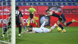 Bek Cagliari, Charis Lykogiannis (kanan) menjatuhkan striker AC Milan, Zlatan Ibrahimovic di dalam kotak penalti dalam laga lanjutan Liga Italia 2020/21 pekan ke-18 di Sardegna Arena, Senin (18/1/2021). Cagliari kalah 0-2 dari AC Milan. (AFP/Alberto Pizzoli)