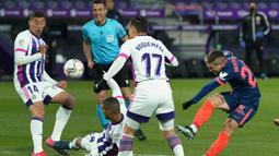 Striker Sevilla, Papu Gomez (kanan) melepaskan tendangan yang masih membentur pemain Real Valladolid dalam laga lanjutan Liga Spanyol 2020/2021 pekan ke-28 di Jose Zorrilla Stadium, Valladolid, Sabtu (20/3/2021). Sevilla bermain imbang 1-1 dengan Valladolid. (AFP/Cesar Manso)