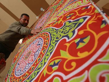 Seorang pria membuat lentera Ramadan tradisional di Kota Khan Younis, Jalur Gaza selatan (19/4/2020). Jelang Ramadan, warga Palestina membeli lentera beraneka warna, yang dikenal sebagai fanoos dalam bahasa Arab, untuk anak-anak mereka atau sebagai hiasan di rumah. (Xinhua/Rizek Abdeljawad)