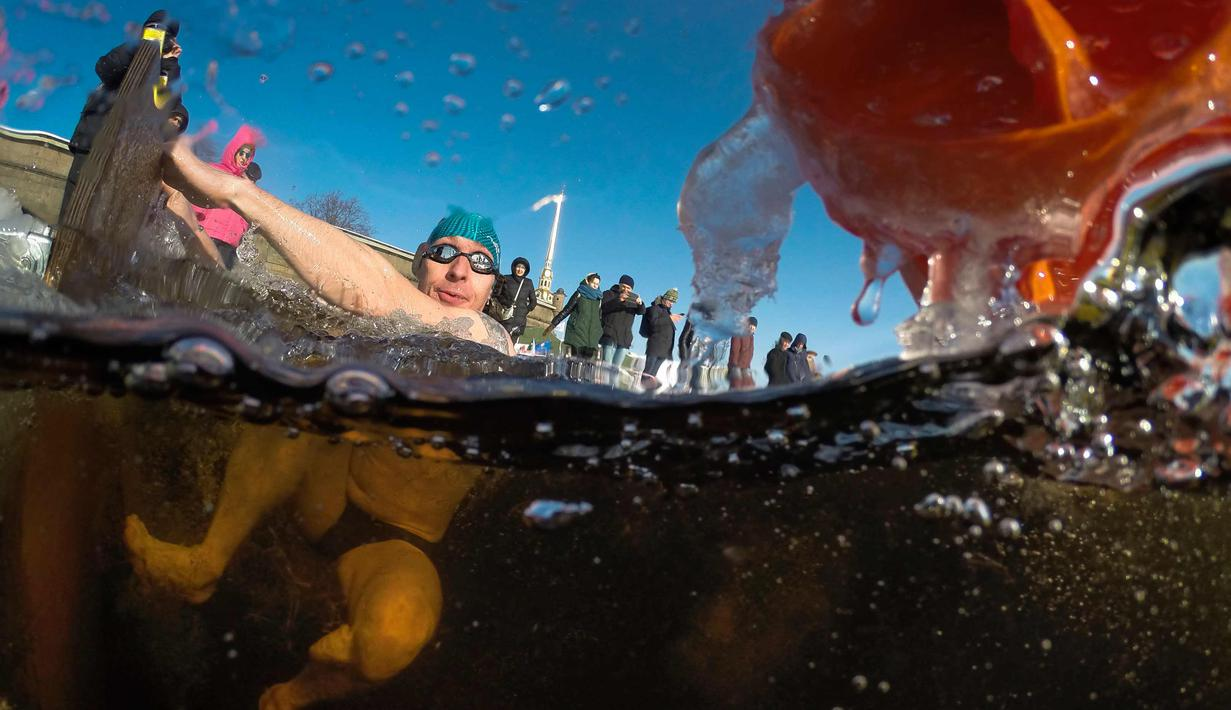 Seorang peserta mengikuti kompetisi renang es Big Neva Cup di sungai Neva di St.Petersburg, Rusia, (4/3). Sekitar 150 peserta mengikuti kompetisi renang dengan suhu minus 10 derajat celcius. (AP Photo/Dmitri Lovetsky)