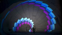 Salah seorang peserta sedang mempersiapkan balon udaranya saat Festival Balon Udara Internasional di Taman Nasional Maayan Harod, Israel (30/9/2015). (REUTERS / Baz Ratner)