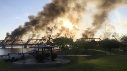 Asap membumbung saat kereta barang tergelincir dan terbakar di jembatan Danau Kota Tempe, Arizona, Amerika Serikat, Rabu (29/7/2020). Kecelakaan terjadi sekitar pukul 06.15 waktu setempat. (Daniel Coronado via AP)