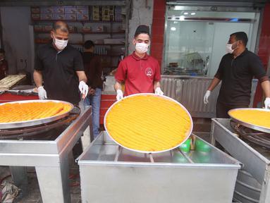 Warga membuat penganan manis tradisional yang dikenal dengan nama Qatayef di Kota Rafah, Jalur Gaza, Palestina, Senin (27/4/2020). Qatayef adalah sejenis makanan penutup yang biasa dibuat saat bulan suci Ramadan. (Xinhua/Khaled Omar)