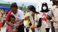 Relawan protokol kesehatan Satgas Penanganan COVID-19 memberikan masker kain kepada warga di sekitar Stadion Barnaban Yumeo, Papua, Senin (27/9/2021). (Dok BNPB)