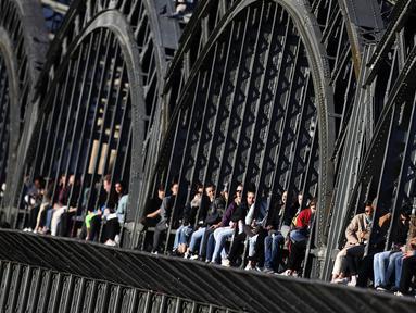 Kaum muda menikmati matahari terbenam di jembatan 'Hackerbruecke' di Munich, Jerman, Minggu, (28/3/2021). Hackerbrücke (Hacker Bridge) adalah jembatan jalan raya yang melintasi jalur kereta api utama di Munich tepat di sebelah barat stasiun pusat kota. (AP Photo/Matthias Schrader)