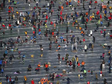 Antusias ribuan warga memancing ikan air tawar melalui lubang kecil selama acara Festival Es di sungai yang beku di Hwacheon, selatan dari zona demiliterisasi (DMZ) yang memisahkan dua Korea, (9/1/2016). (REUTERS/Kim Hong-Ji)