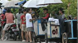 Sejumlah warga menunggu pakaiannya yang sedang dikecilkan oleh penjahit keliling di kawasan Lenteng Agung, Jakarta, Senin (4/7). Menjelang hari raya Idul Fitri, penjahit 'vermak levis' keliling mulai kebanjiran rezeki. (Liputan6.com/Yoppy Renato)