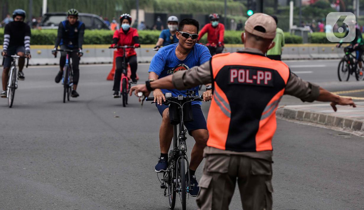 Satpol PP menghentikan pesepeda yang tidak mengenakan masker saat melintas di kawasan Bundaran HI, Jakarta, Minggu (17/1/2021). Pemerintah terus melakukan berbagai upaya guna mencegah penyebaran COVID-19 dan menurunkan angka masyarakat yang terpapar virus corona. (Liputan6.com/Johan Tallo)