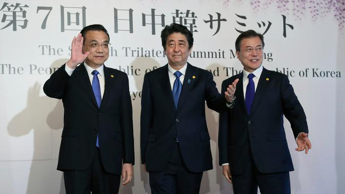 Perdana Menteri China Li Keqiang, Perdana Menteri Jepang Shinzo Abe dan Presiden Korea Selatan Moon Jae-in menyapa awak media usai melakukan pertemuan tingga negara di Tokyo, Jepang (9/5). (AP Photo/Eugene Hoshiko, Pool)