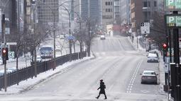 Seorang perempuan mengenakan masker saat melintasi jalan raya Rene-Levesque di Montreal, Kanada, Minggu (10/1/2021). Pemerintah Quebec memberlakukan lockdown dan jam malam untuk membantu menghentikan penyebaran COVID-19 yang berlangsung hingga 8 Februari. (Graham Hughes/The Canadian Press via AP)